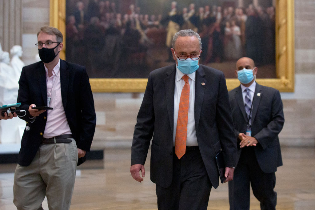 Chuck Schumer walks in the Capitol rotunda flanked by two men.
