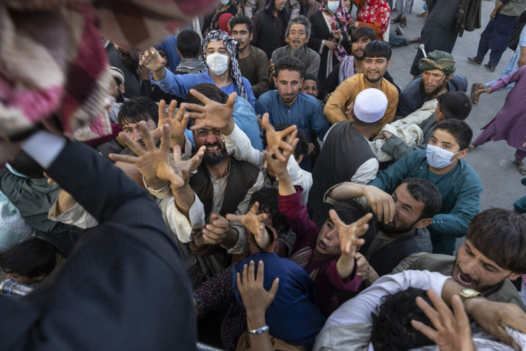 Displaced Afghans reach out for aid from a local Muslim organization at a makeshift IDP camp on Aug. 10 in Kabul, Afghanistan.