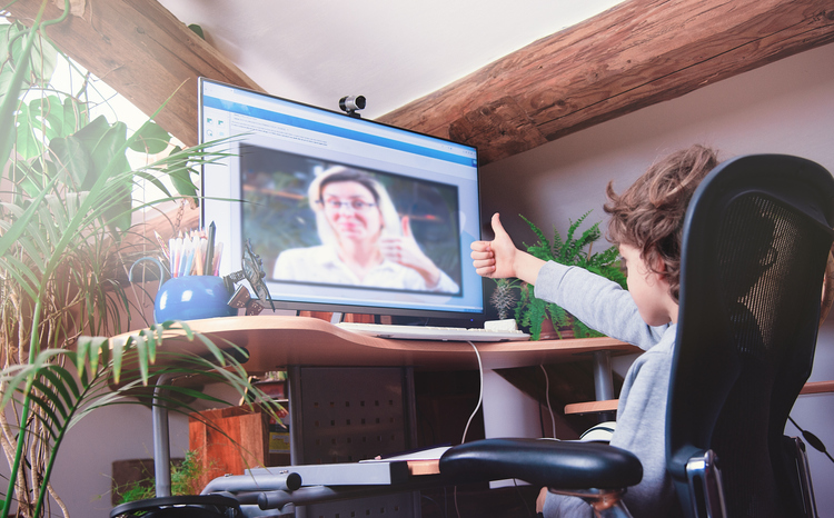 A young boy gives the thumbs up to a teacher on his computer screen during online schooling