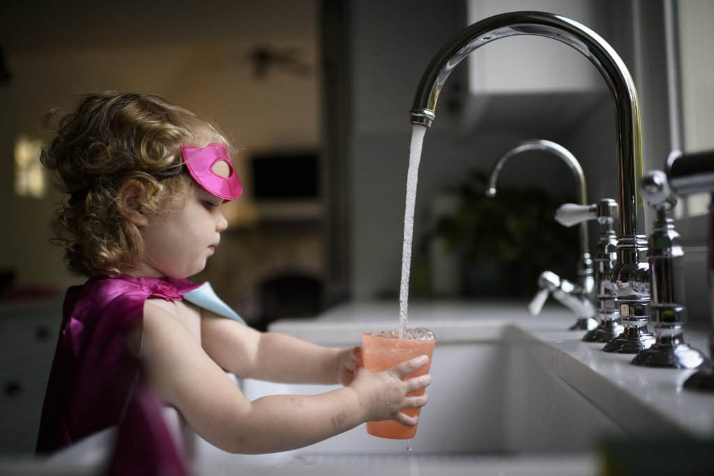 A young girl fills a glass of water at a kitchen sink