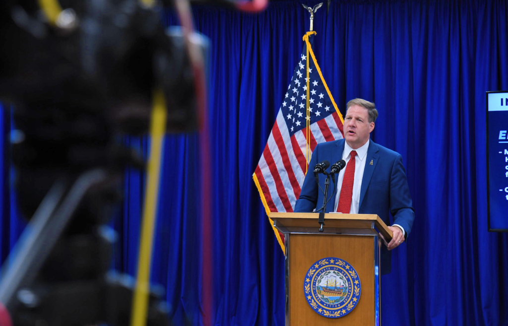 Chris Sununu stands at a lectern with an American flag behind him
