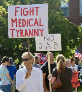 Protesters hold signs during an anti-vaccine mandate rally