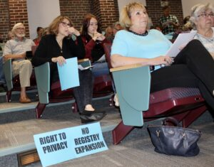 People opposed to changes to the vaccine registry sit during a public hearing