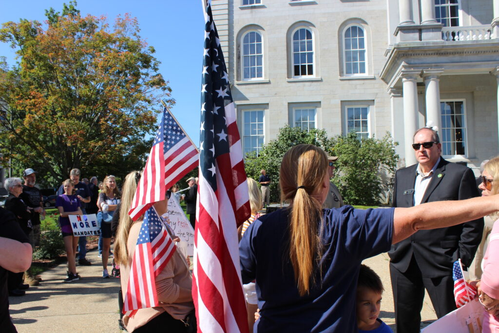A woman standing near American flags, her back to the camera, yells at a lawmaker during a rally in front of the State House