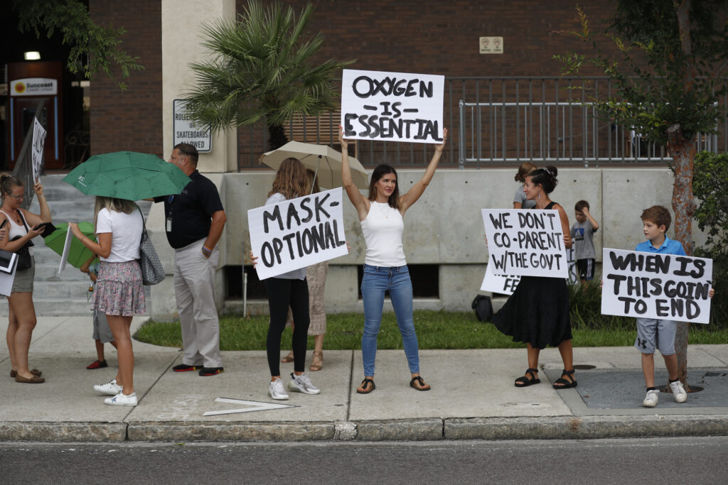People protest mask mandates in Florida by holding up signs
