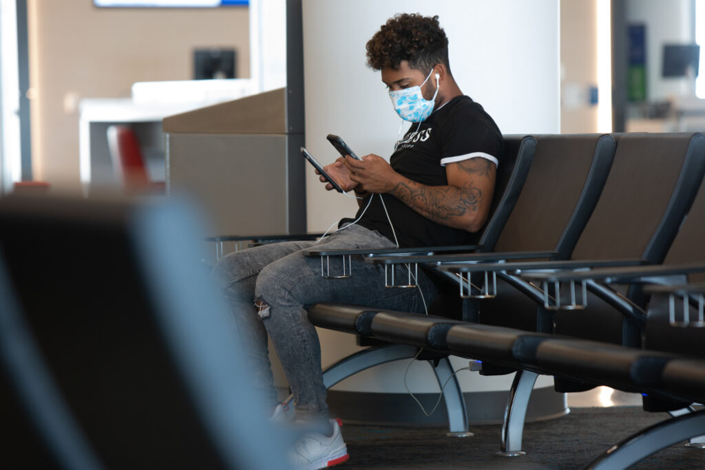 A man sits alone at an airport wearing a mask and looking at his phone
