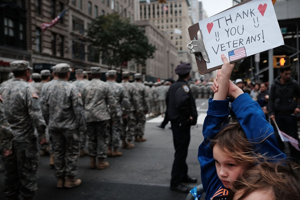 A child holds up a sign thanking veterans during a parade