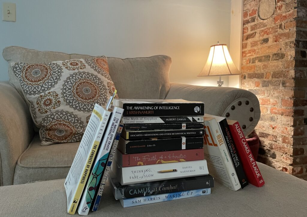 A stack of books near a chair and lamp