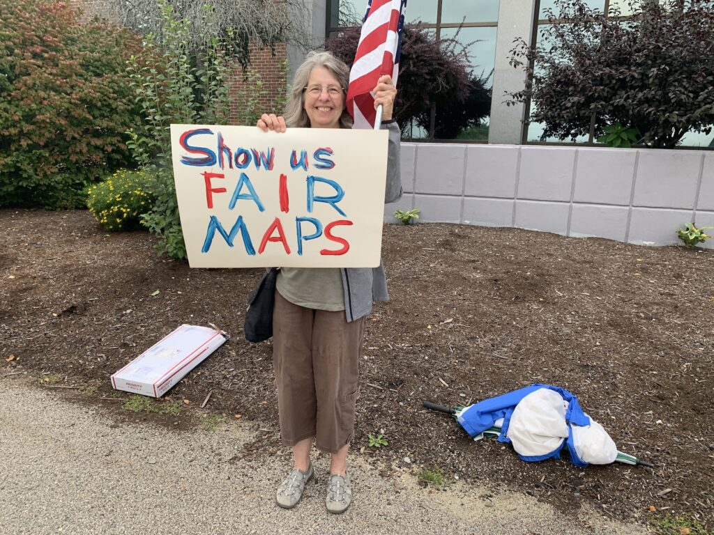 """A woman holds a sign that reads """"Show us fair maps"""""""