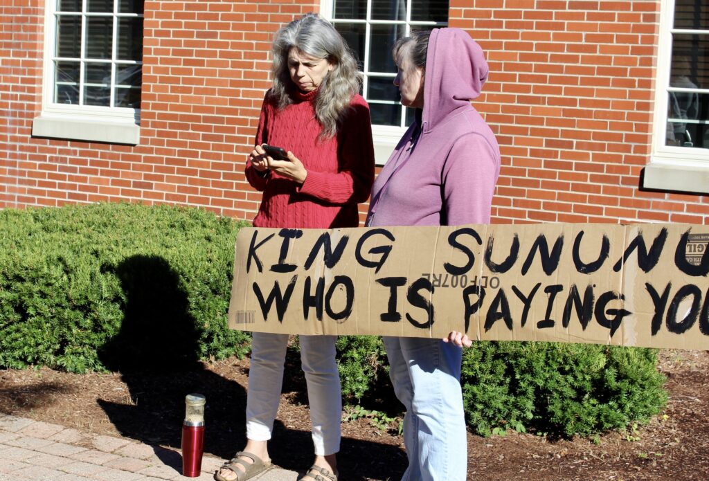 """Two women stand outside of a brick building with a sign reading """"King Sununu Who is Paying You"""""""