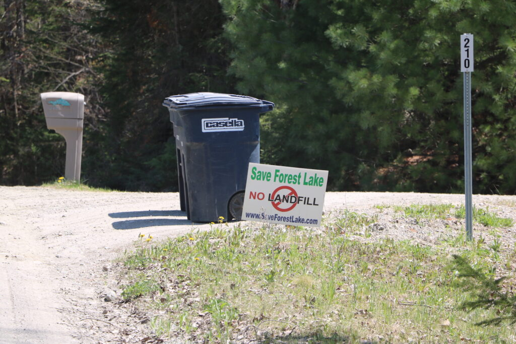 A trash can and a sign opposing the landfill at the end of a driveway