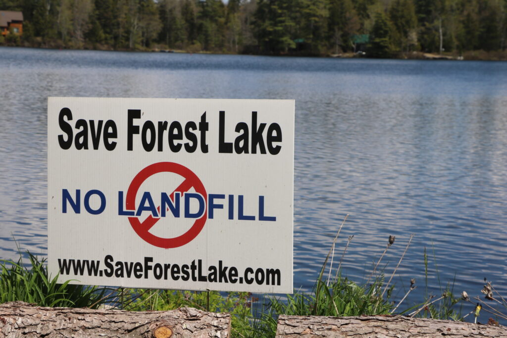 A sign protesting the proposed landfill, with forest lake in the background