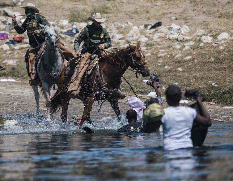 Border agents on horseback confront Haitian migrants in a river