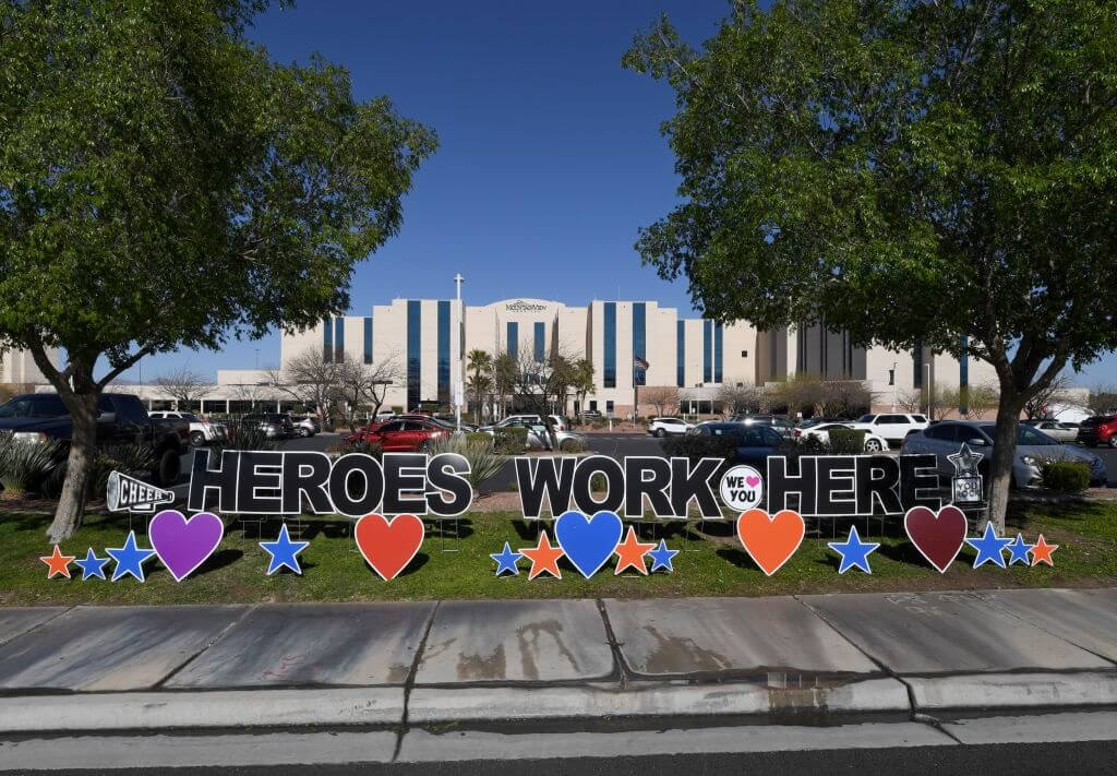 """A sign outside of a hospital reads """"Heroes work here"""""""