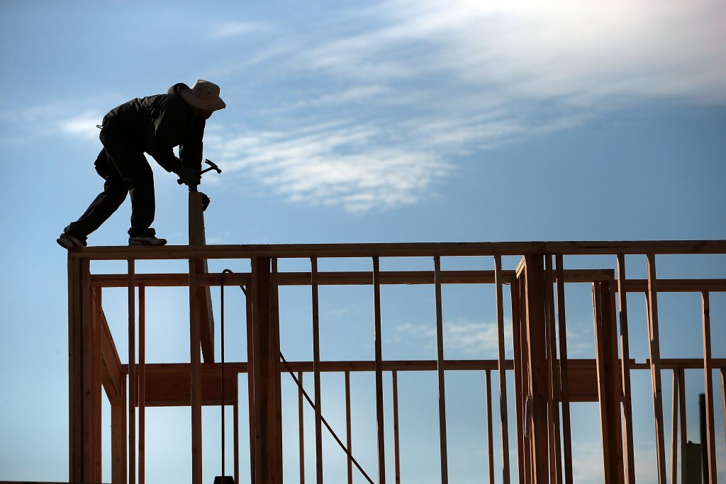 A construction worker stands atop a house frame
