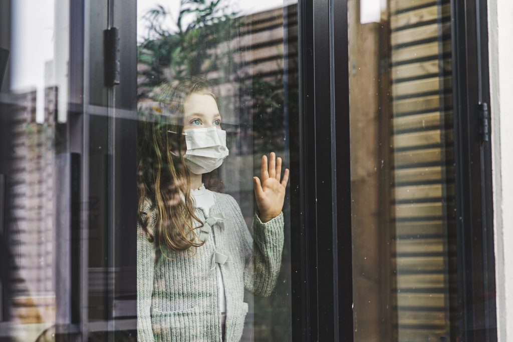 A girl with a mask looks out the window