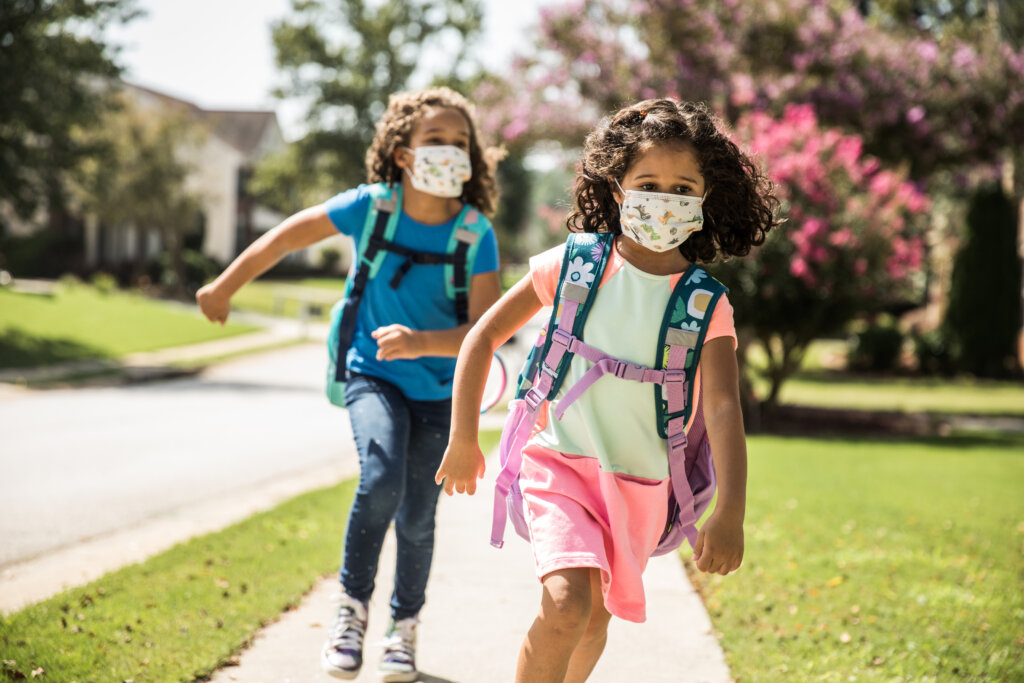 Young girls running on a sidewalk wearing protective masks