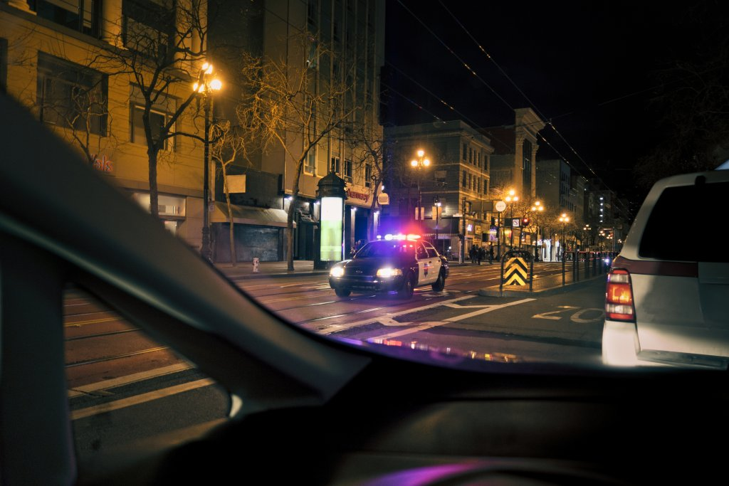A police car with its lights on at night on a city street