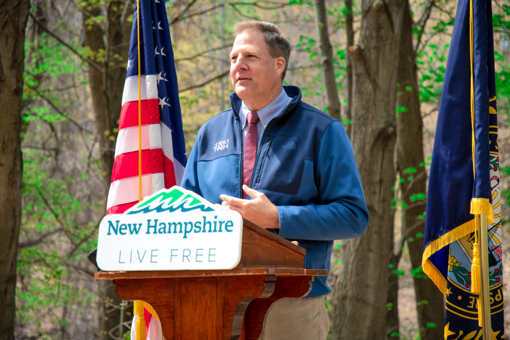 Gov. Chris Sununu stands at a lectern outside on Friday