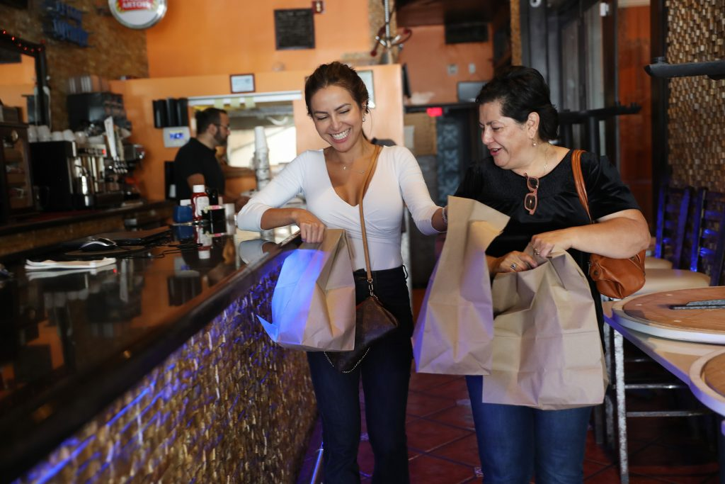 Two women carry paper bags of takeout food as they leave a restaurant