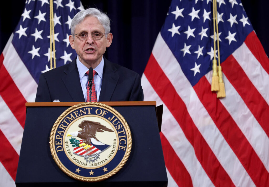 Merrick Garland at a lectern with American flags in the background