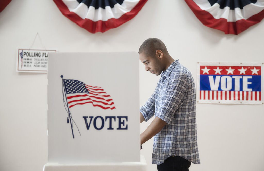 A man stands at a voting booth