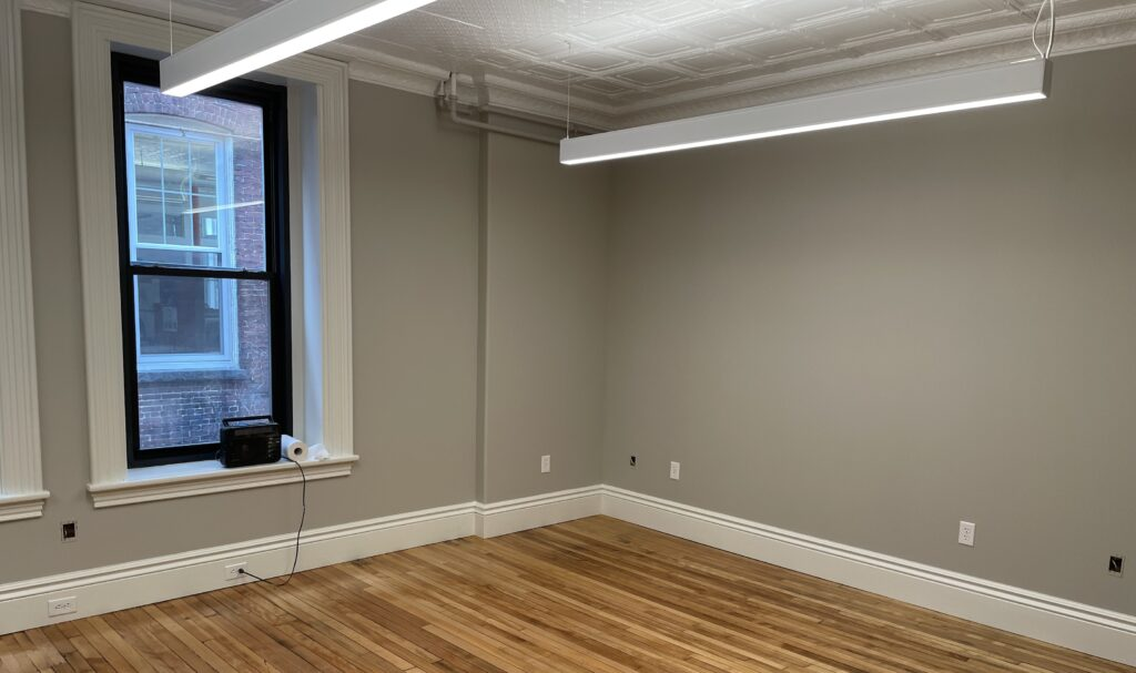 The corner of a small room, with hardwood floors
