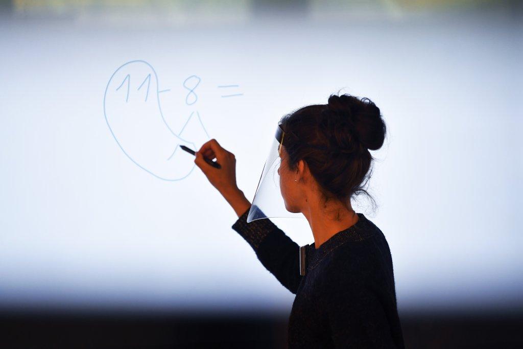 A teacher writes on a white board